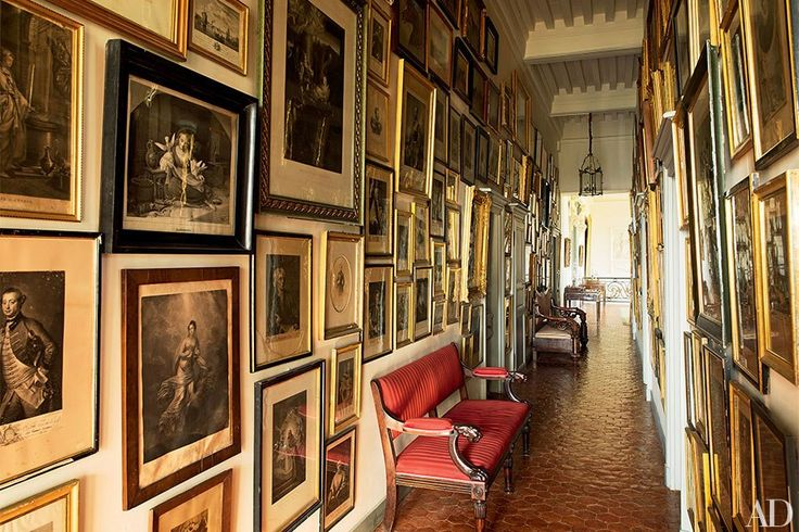 Antique etchings line a second-floor hall; the settee in the foreground is George III, and the floor is paved with terra-cotta tiles.