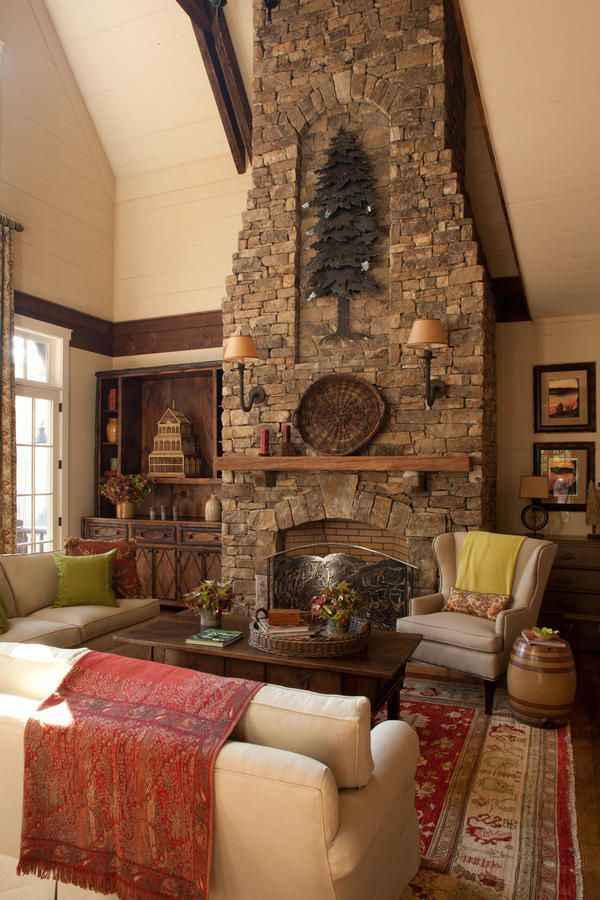 A stacked fieldstone fireplace takes center stage in this family room. Rather than just a sheer wall of stone, the exposed chimney is designed with a central recess for artwork, along with tapered edges on either side, to keep it from appearing too overpowering. Sconces mounted directly to the stone are an attractive way to shed plenty of light on the antique timber mantel.  Living Room Finishing Touches