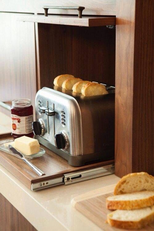 Toaster behind a cupboard door on a rolling board to slide out when in use.