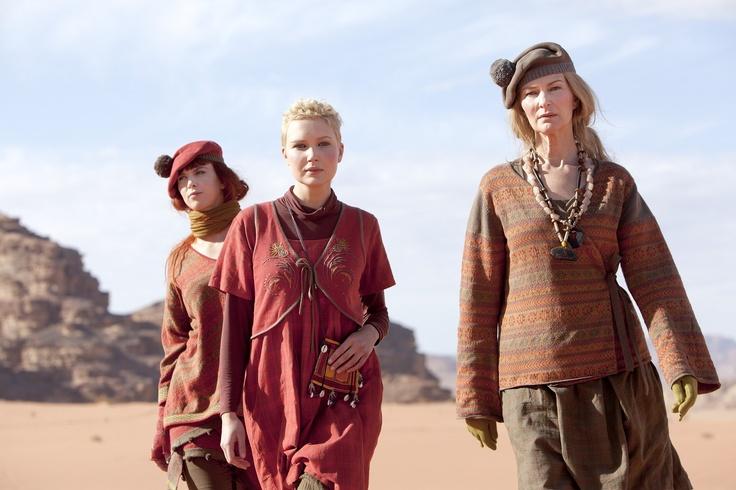 """Herbstmode 2012 - Kollektion 'schottisches Hochland': Die Kollektion """"schottisches Hochland"""" in Borke & Krapprot auf einem Blick. Das linke Model trägt einen Baumwollpullover mit Jacquardstrick und V-Ausschnitt. In der Mitte ist ein Bolero aus Bumwolle, der über einem karierten Kleid aus Öko-Baumwolle getragen wird, zu sehen. Das Model auf der rechten Seite präsentiert eine Wickeljacke mit Jacquarstrick, dazu einen karierten Rock aus Öko-Baumwolle & eine Bommelmütze."""