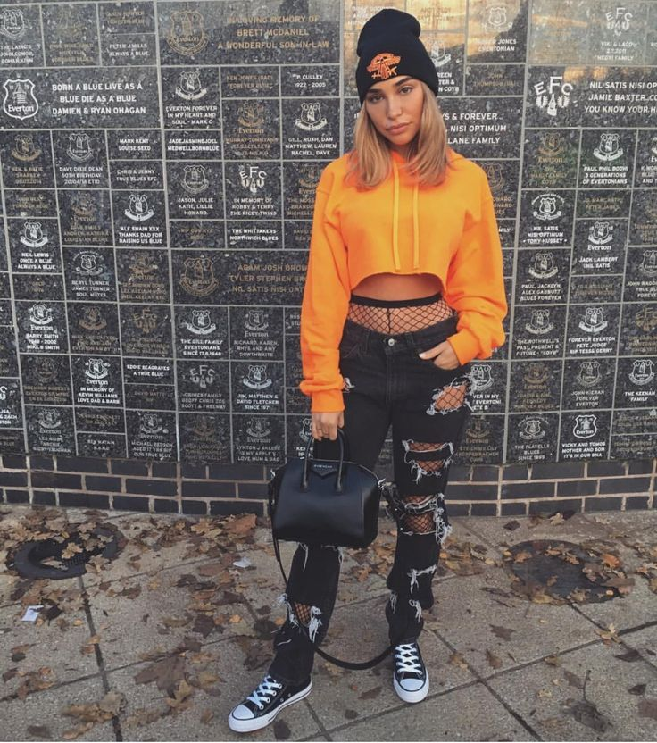 Chantel Jeffries wore ripped denim over fishnets, adding a bright orange hoodie and a beanie.