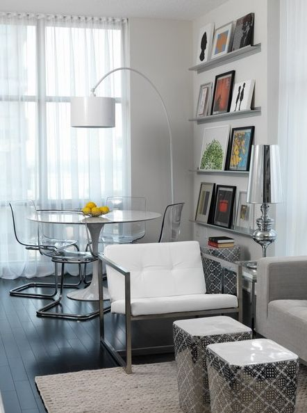 Toronto Interior Design Group    Open living/dining space with marble top Saarinen Dining Table, Ikea Tobias Chairs, white vinyl drum arc floor lamp, stainless steel slim profile floating book shelves and gray walls paint color.