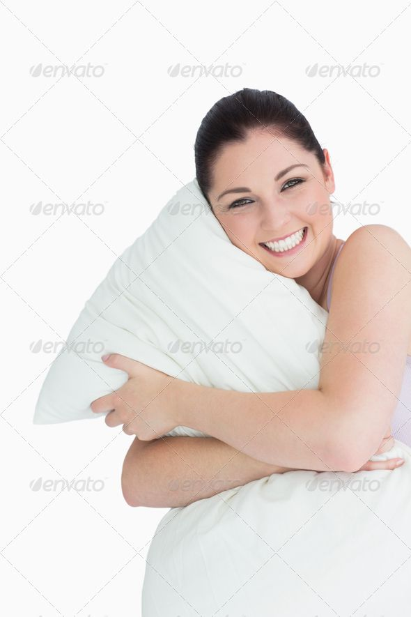Happy woman hugging a pillow on white background ...  20s, Looking At Camera, black hair, brown hair, brunette, caucasian, cheerful, clutching, copy space, cushion, dark hair, female, happy, hugging, indoors, pillow, pyjamas, relaxation, smiling, tied hair, white background, woman, young adult