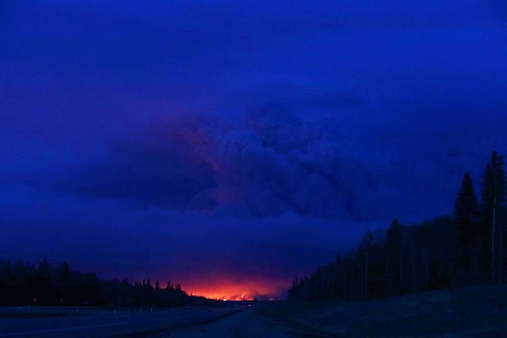 A plume of smoke hangs in the air as forest fires rage on in the distance in Fort McMurray, Alberta on May 4, 2016.