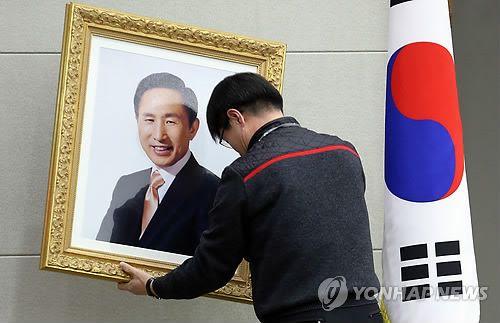 내려지는 이명박 대통령 사진 : 박근혜 대통령의 취임식이 열리는 25일 오전 서울 국방부 대회의실에서 한 관계자가 이명박 대통령의 사진을 내리고 있다.