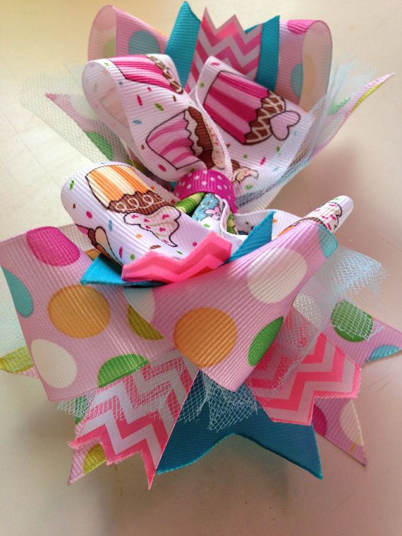 This deliciously cute cupcake hair bow is perfect for any little birthday girl in your life. It is stacked using pink multi color polka dot ribbon, sky blue ribbon, pink and white chevron ribbon, blue tulle, and multi color cupcake ribbon. It is attached to a ribbon lined alligator clip