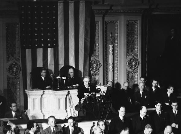 Declaring Japan guilty of a dastardly unprovoked attack, U.S. President Franklin D. Roosevelt asked Congress to declare war, on December 8, 1941. Listening are Vice President Henry Wallace, left, and House Speaker Sam Rayburn.