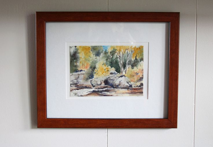 watercolour of northwestern Ontario in wood frame hung on white wall