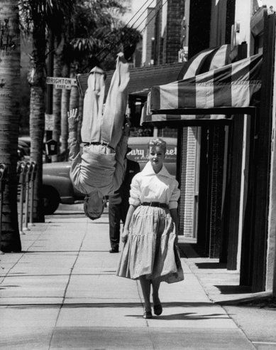 Acrobat and actor Russ Tamblyn does a flip on the sidewalk while walking with Venetia Stevenson in 1955