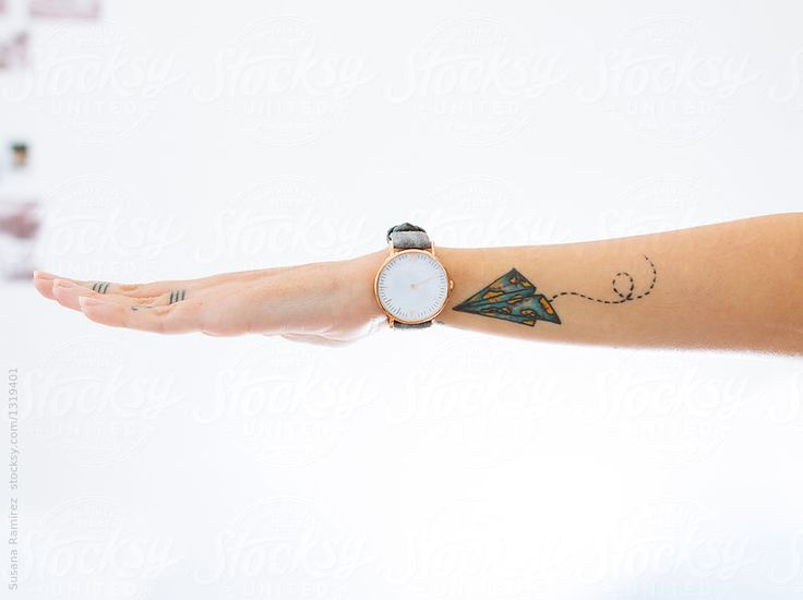 Detail of arm with wrist watch and a tattooed airplane by Susana Ramírez for Stocksy United