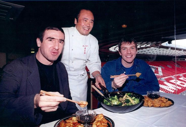 Chinese Chef Ken Hom introduces Manchester United Footballers Eric Cantona and Lee Sharpe to the Art of Chinese food at the Old Trafford Football ground .