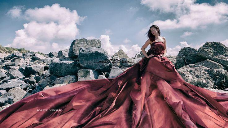 Dress to impress # RobSteunenberg #red #dress #beach #photoshop #rocks #model #beauty #sun #clouds #brownhair #beachshoot #biggdress #beautyful