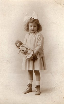 Antique photo postcard of darling little girl with her doll, circa 1910.