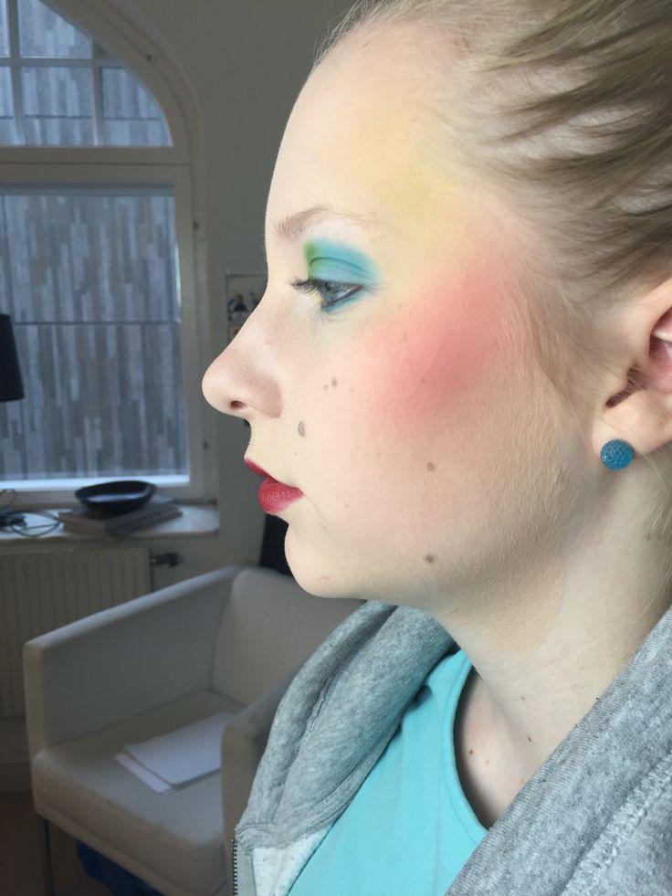 Först gjorde jag basen och korrigeringen, Sedan använde jag mig av suddade bryn för att fylla i ögonbrynen, Efteråt tog jag en blå & grön färg & la på lockskuggan & globskuggan & gjorde där efter en fransmarkering, Sedan la jag en blå droppskugga under hennes ögon och la en gul & röd färg på sidorna av hennes ansikte.   Till sist tog jag mascara på fransarna & en ljusröd färg på hennes läppar.