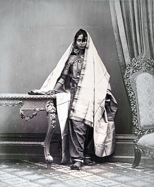 Portrait of a Muslim girl from Sindh, showing method of wearing ear and nose rings, necklace and anklets    Full-length standing studio portrait of a Muslim girl from Karachi in Sind, Pakistan, taken by Michie and Company in c. 1870