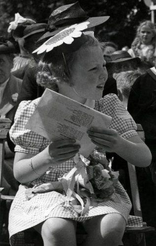 Soestdijk (Nederland) Prinses Beatrix op het tuinfeest t.g.v. de verjaardag van Prins Bernhard, haar vader.Zij heeft een mooie feesthoed op, gemaakt van papier voorstellende een zonnebloem. Ze heeft een ruit jurkje aan. Op haar schoot heeft zij een boeketje bloemen. Zij heeft een blaadje in haar hand met een feestlied erop. Zij zit ingespannen naar iets te kijken. 29 juni 1946 .