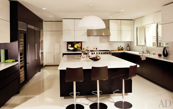 Celebrity chef Giada De Laurentiis's kitchen boasts ample storage and work space, including an oversized island with white-marble countertops, Poliform cabinetry, Viking appliances, and white concrete floors.