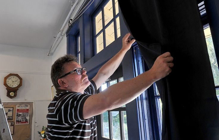 MARIO BARTEL/THE TRI-CITY NEWS Markus Fahrner, the director of the Port Moody Station Museum, begins hanging blackout drapes to cover the old train station's windows to create a light-controlled environment for a valuable album of photos, sketches and letters by Mary Moody, the wife of Colonel Richard Moody who founded the city.