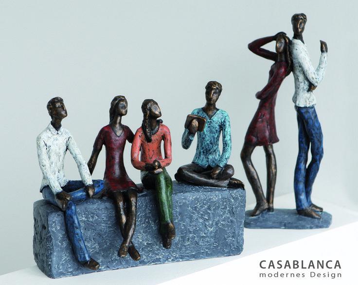 """Skulptur """"Network"""" aus Poly · mit farbigen Kleidungsstücken auf grauer Basis Tiefe 11 cm, Breite 26 cm, Höhe 21 cm  Skulptur """"Contact"""" aus Poly · bronzefarben/rot/blau/weiß auf grauer Basis Breite 13 cm, Höhe 30 cm"""