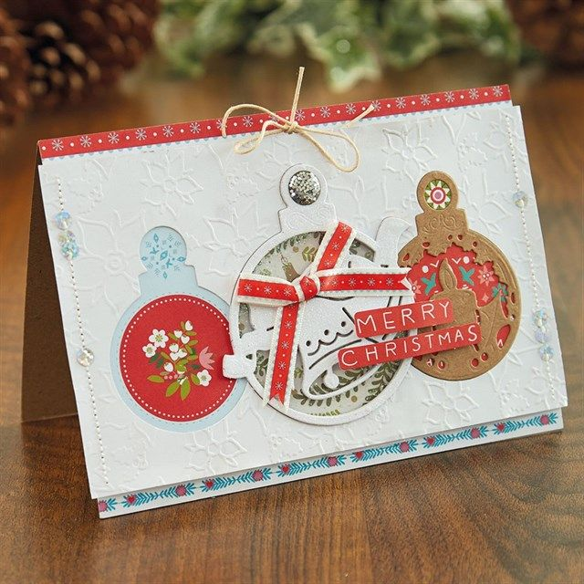 Using a cool combination of patterned papers, apertures and die-cut shapes, this die-cut Christmas card has something different in every bauble. The results are stunning and the same method can be applied to any number of handmade cards.Layered Bauble Christmas Card Tutorial | docrafts.com
