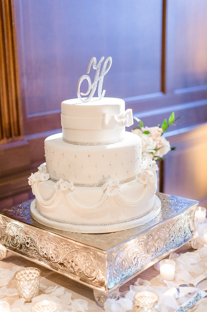 All white three tiered cake with white detailing on silver cake stand with white rose petals topped with silver jeweled initial | Leslie Ann Photography | villasiena.cc