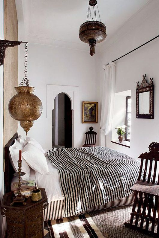 bohemian Moroccan inspired bedroom with ornate lamps and white washed walls | kilim rug | White bedding with a striped bedspread | get inspired and make the look your own with a striped black and white Bemz bedspread