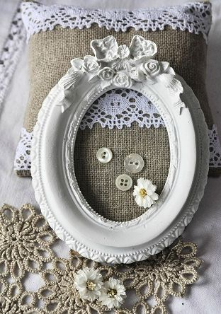 burlap and lace pillows with an old frame and some shell buttons