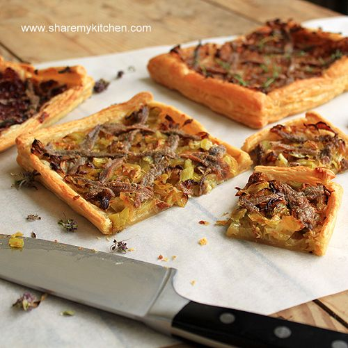 Pissaladiere - a traditional French appetizer -  a simple white pizza with olives, anchovie paste, caramelized onions