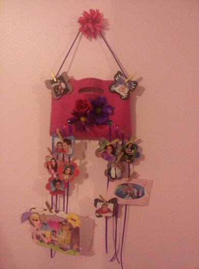 Felt clutch dressed with flowers, acrylic stones and ribbon to display photos.  Pictures are glued to painted wood flowers and butterflies and hung with small clothes pins.  Pins are spray painted gold. Items can be stored in the clutch as well.