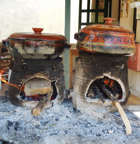 Cretan traditional cooking method using earthenware pots on open fires of burning olive wood.
