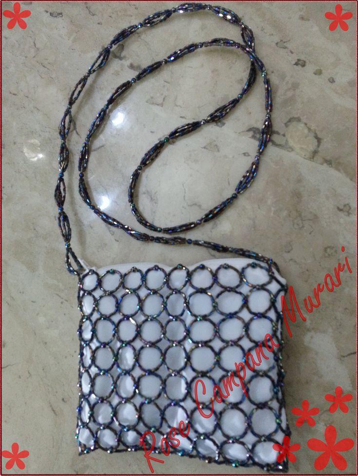 Bolsa em micro-canutilhos e miçangões, feita com linha de nylon; 17 cm por 14 cm de tamanho. Forro externo de tafetá, com manta acrílica e voal como forro interno.