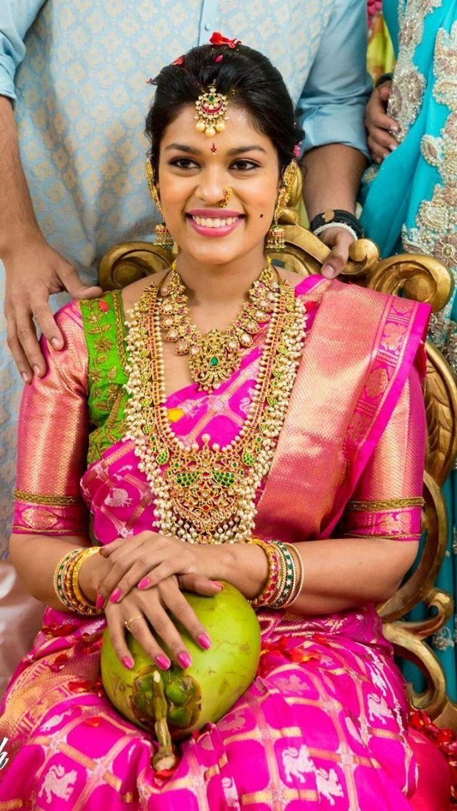 South Indian bride. Gold Indian bridal jewelry.Temple jewelry. Jhumkis. Pink silk kanchipuram sari.Braid with fresh jasmine flowers. Tamil bride. Telugu bride. Kannada bride. Hindu bride. Malayalee bride.Kerala bride.South Indian wedding.Sreeja.