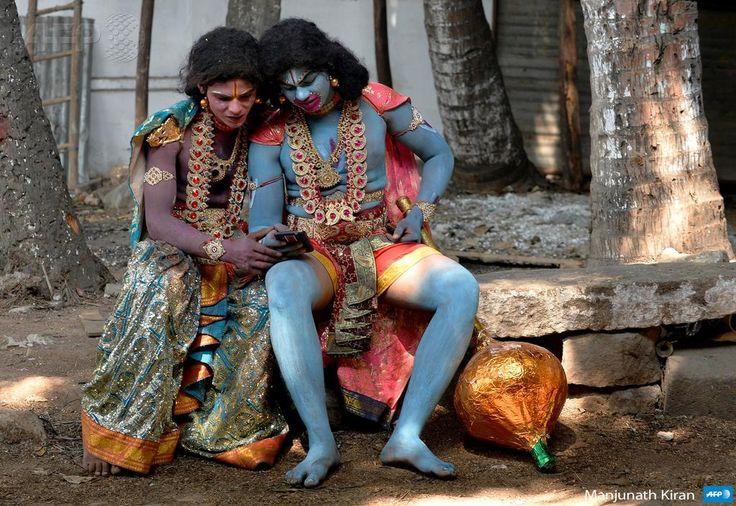 Deux hommes costumés en divinités hindoues regardent une vidéo sur un mobile à Bangalore. Par @manjunath_kiran #AFP