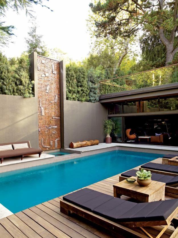 Piscina com sofá em madeira e colchões impermeáveis sobre o deck