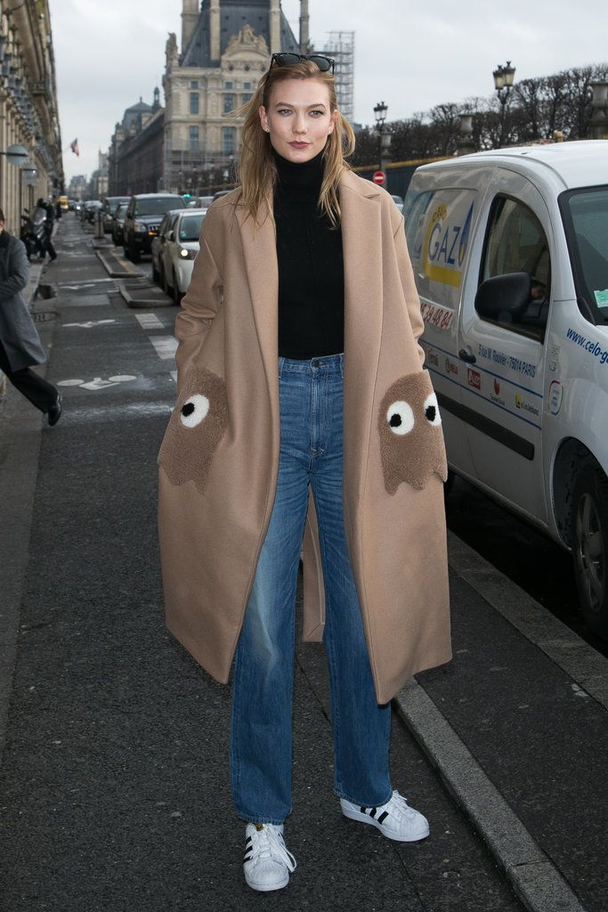 Karlie Kloss in an Anya Hindmarch coat, straight leg jeans, and white sneakers.