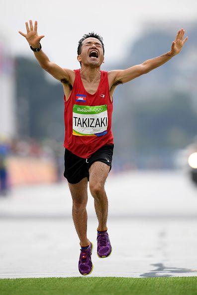 Kuniaki Takizaki of Cambodia reacts as he crosses the finish line during the…