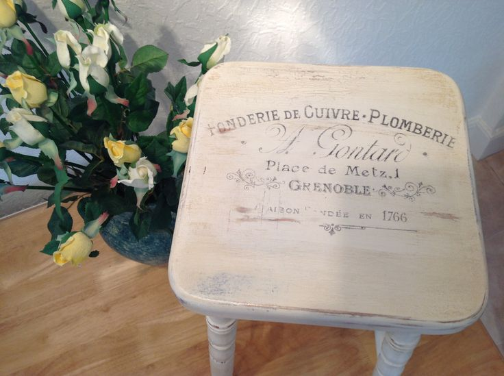 THIS IS A MODERN PINE STOOL. IT HAS BEEN PAINTED BLUE AGED AND CRACKED AND THEN PAINTED CREAM AND AGED AGAIN TO REACH AN OLD WORN APPEARANCE.  A FRENCH INK PRINT HAS BEEN APPLIED AND RUBBED BACK TO COMPLETE THE WORN LOOK