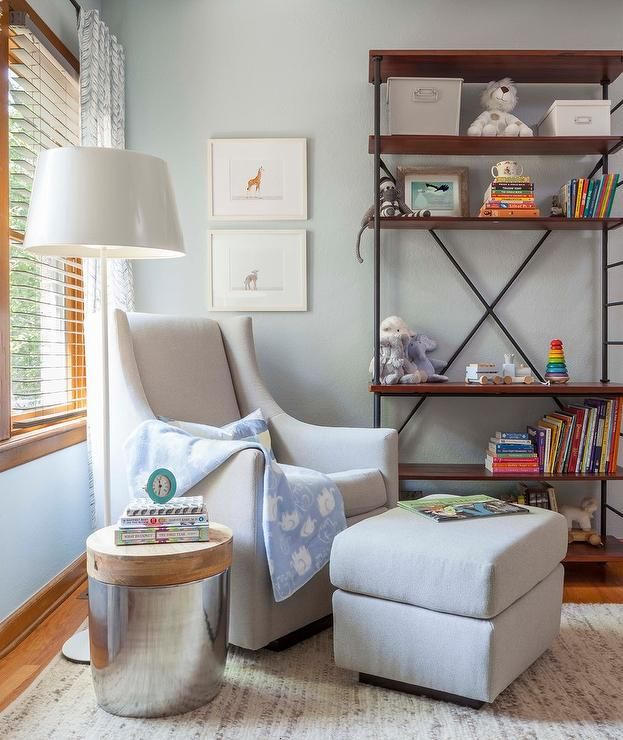 Well appointed nursery boasts a PB Kids Merced Glider & Ottoman placed on a gray and gold jute rug beside a glossy white floor lamp placed behind a wood and steel accent table.