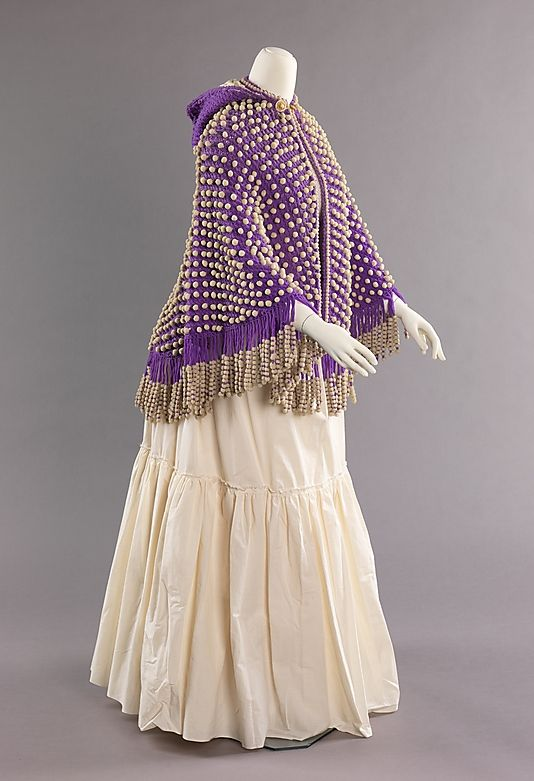 """Cape: 1873, American, wool. """"This intriguing cape was exhibited at the Vienna Universal Exhibition in 1873. Its elaborate knitting techniques and unique overall appearance enforce the importance of handmade crafts and decorations which were becoming progressively important nearing the end of the 19th century."""""""