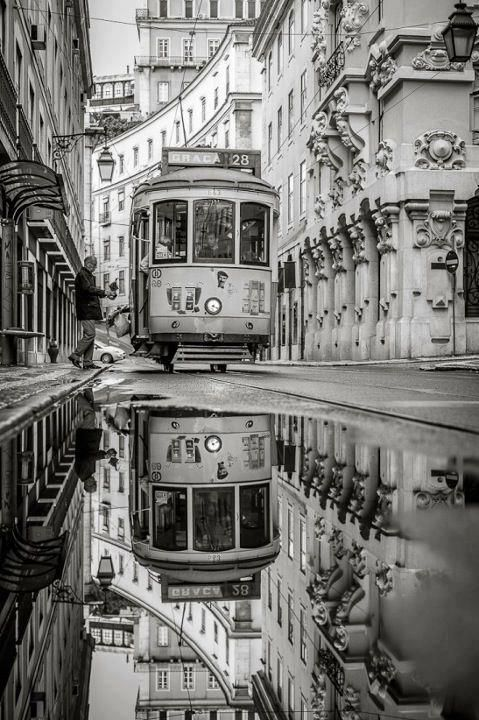 Streetcar beautifully reflected in a large water puddle. Lisbon, Portugal.