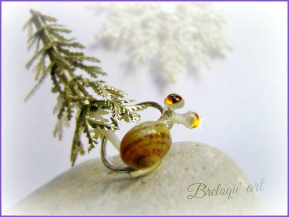 Bague escargot fait main, modèle original et unique, l'anneau est en en plaqué argent et l'escargot est réalisé avec une véritable coquille d'escargot petit gris.  Le corps de l'escargot à été modelé à chaud en une pâte polymère semi- transparente, rigidifiée.  L'escargot a revêtu un habit de lumière pour les fêtes! La coquille et   son corps sont légèrement recouverts d'un verni pailleté et ses yeux sont deux strass jaune-orangé!  Hand made, snail ring, spangled ring.  Taille 52-53
