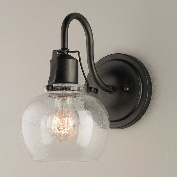"This rustic industrial revolution inspired wall sconce adds traditional lines to urban spaces.  Finished in Rustic iron and featuring glass in clear seeded finish.(10.25""Hx6""Wx9.75""D).  5.5"" round backplate.  Supplied with 8"" of wire.  100 watt medium base bulb max."