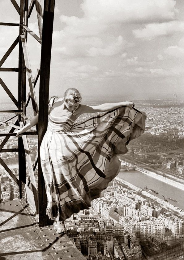 Lisa Fonssagrives wearing dress by Lucien Lelong in death-defying pose high atop the Eiffel Tower overlooking the city of Paris. Photo by Erwin Blumenfeld, French Vogue, May 1939