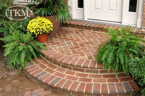 Curved brick entry way porch landing steps in a combination of herringbone, running brick, and standing soldier. Soft bull nose edge. All in all ... a talented and skilled mason worked out this design. Maybe not a DIY for a beginner.
