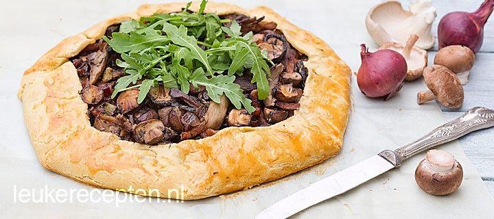 Rustieke taart van paddenstoelen, spekjes en tijm met een krokante half dichtgevouwen deegrand