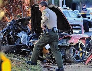 A sheriff's deputy at the scene of a crash in Valencia, Calif., where Paul Walker and another person were killed when a Porsche crashed Saturday.