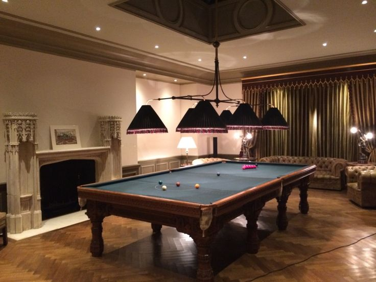 Deep green pleated lamp shades above billiard table