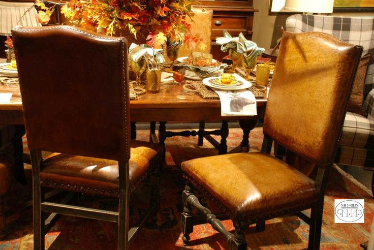 Love this look for a dining room at Nell Hill's - leather side chairs paired with plaid wing back host and hostess chairs.