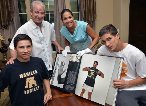 Photo by Jann Hendry ... Biaggio Ali Walsh (right) with his brother, Nico, along with their father, Bob Walsh, and mother, Rasheda Ali-Walsh, look through a book highlighting the boxing career and life of family patriarch Muhammad Ali. Biaggio is a star freshman running back for Bishop Gorman in Las Vegas.