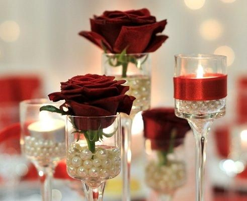Red Wedding Centerpieces ~ Pretty Pearls  Elevated votive or tea light candle holders are an elegant choice to arrange as a centerpiece. Pearls or pearl-like beads can fill the bottom half of each holder, and a single rose bloom or candle can be added to the top for a finishing romantic touch.